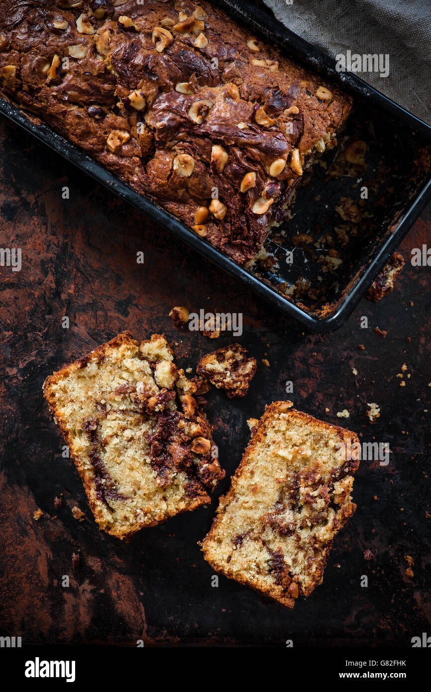 Top view of banana bread with Nutella swirl and chopped hazelnuts on a dark background.  Dark food photography. - Stock Image