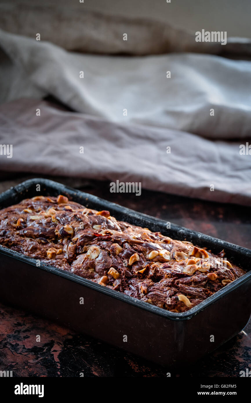 Banana bread with nutella swirl and chopped hazelnuts in the baking pan.  Dark food photography. Free text space. - Stock Image