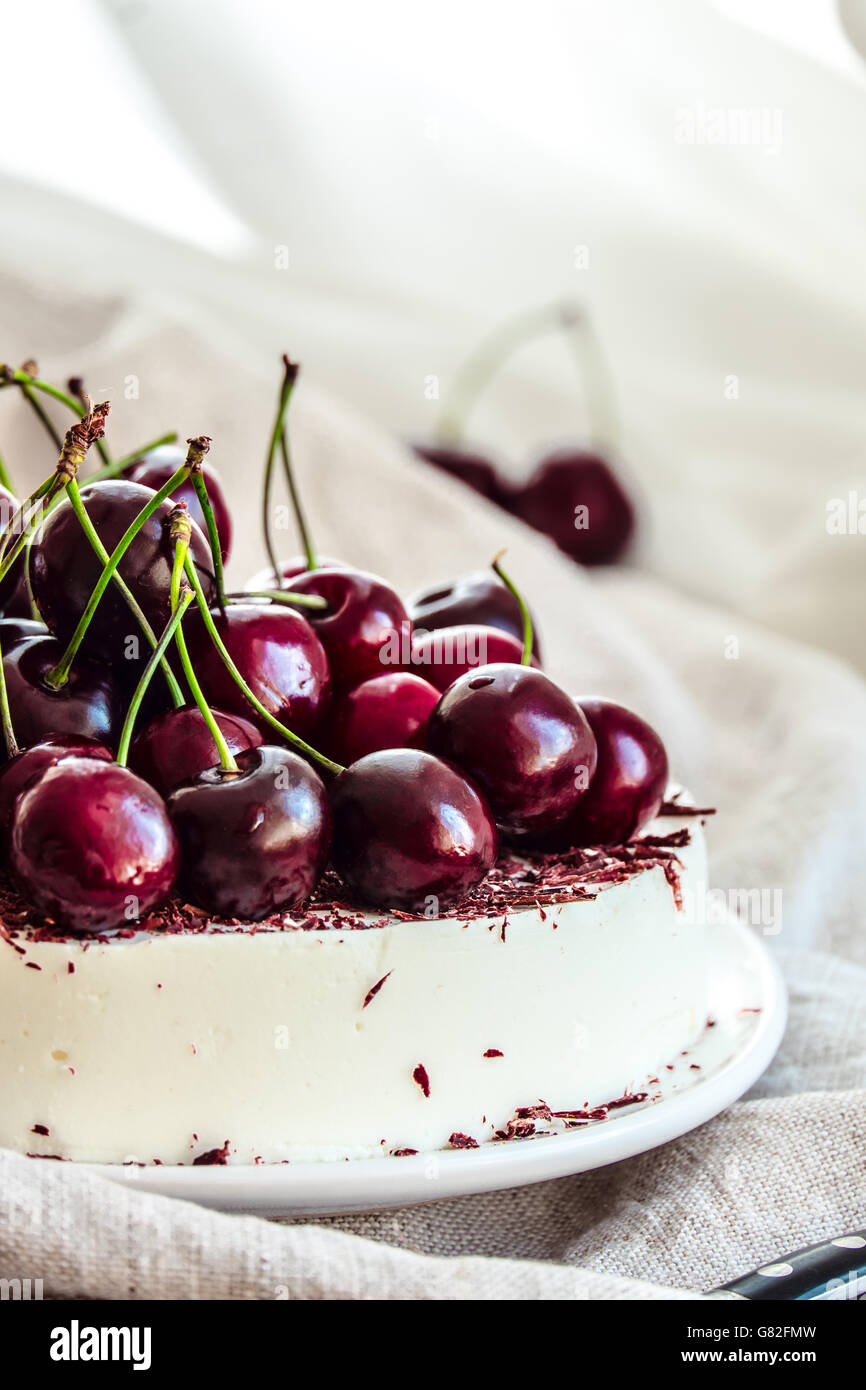 Bavarian mousse cake with cherries and dark chocolate on top. Made with cream cheese and whipped cream. - Stock Image