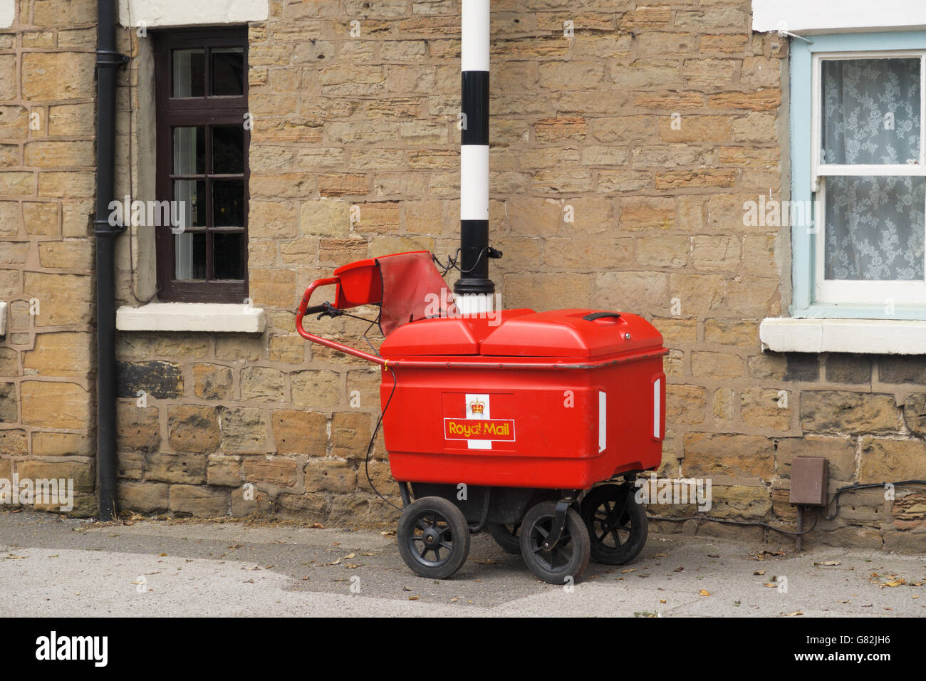A Royal Mail high capacity trolley chained to a post. - Stock Image