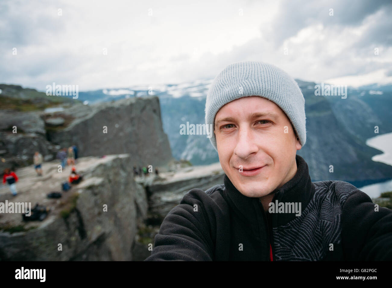 Young Tourist Taking Selfie Against The Backdrop Of The Norwegian Mountains Trolltunga. Troll's Tongue Rock - Stock Image