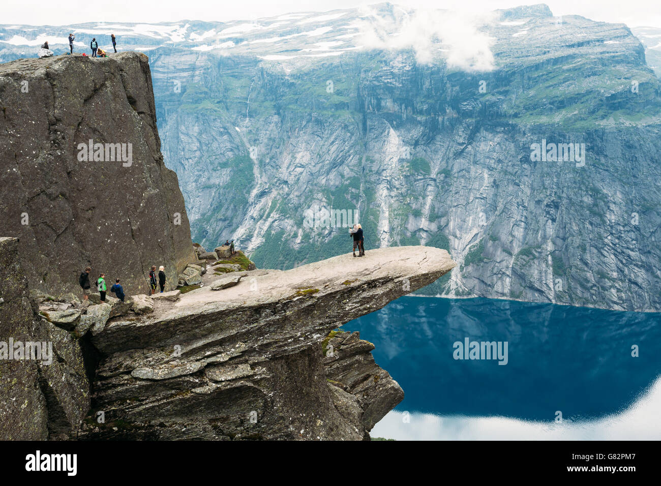 Odda, Norway - August 04, 2014: Young People Are Photographed Standing On A Rock Trolltunga - Troll Tongue In Norway - Stock Image