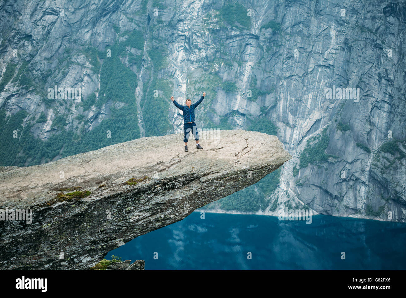 Young Man Standing On Rock In The Mountains Of Norway. Natural Attractions Of Trolltunga - Troll Tongue. - Stock Image