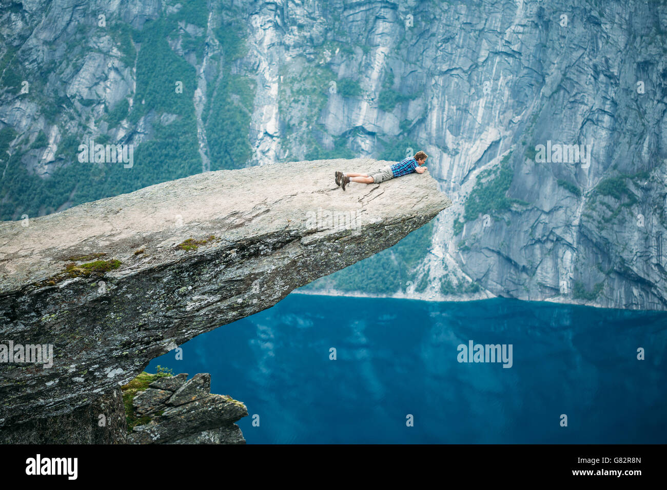Odda, Norway - August 04, 2014: Young Man On Rock Clings To The Edge Of A Cliff And Looking Down In The Mountains - Stock Image