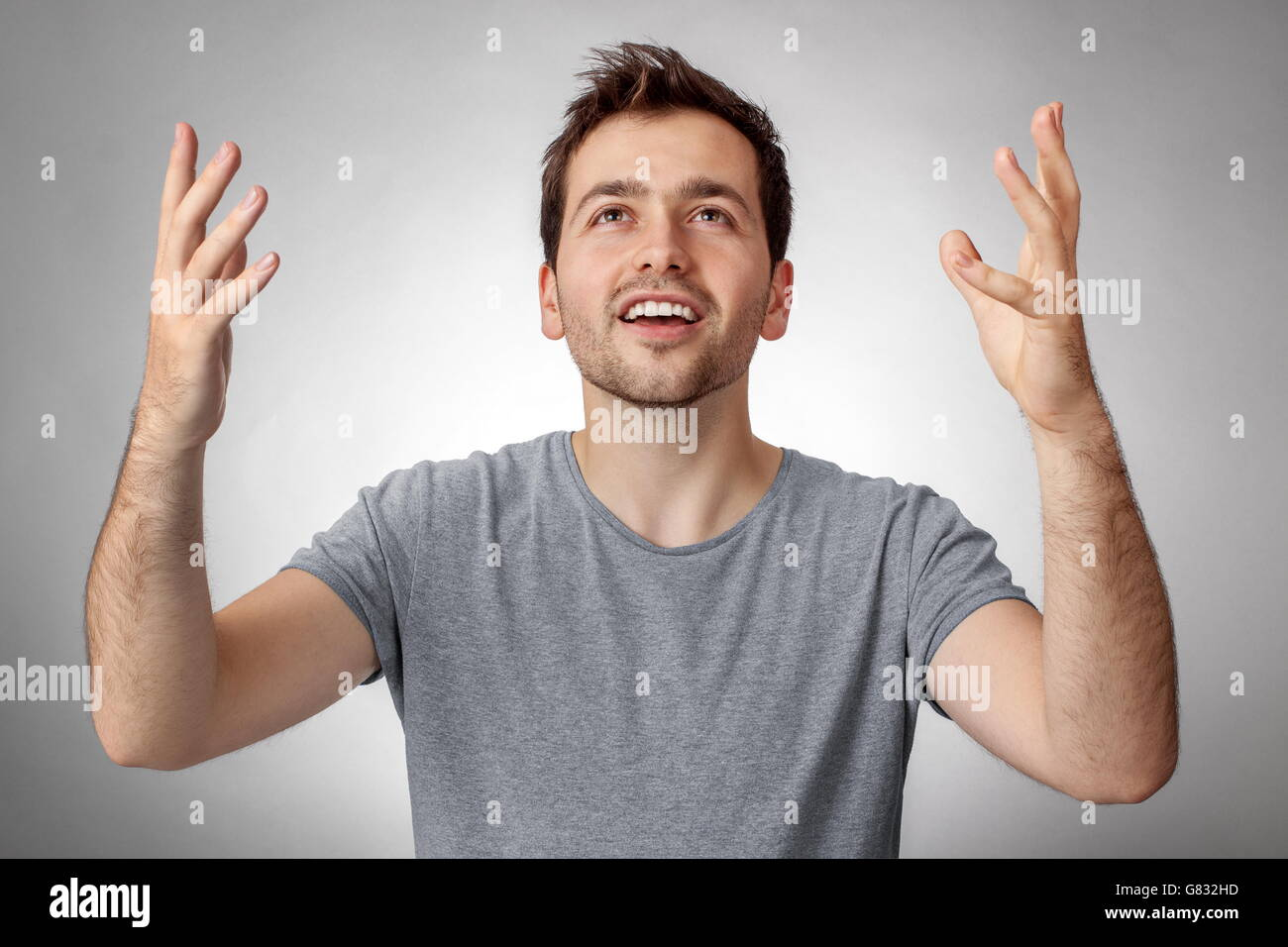 Young man looking up and worship God with raised hands - Stock Image