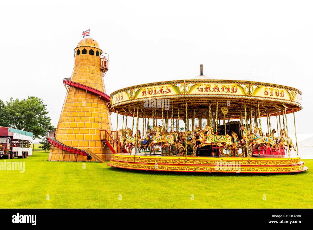 Helter skelter merry go round fair fairground rides ride attraction attractions fairs UK England GB Stock Photo