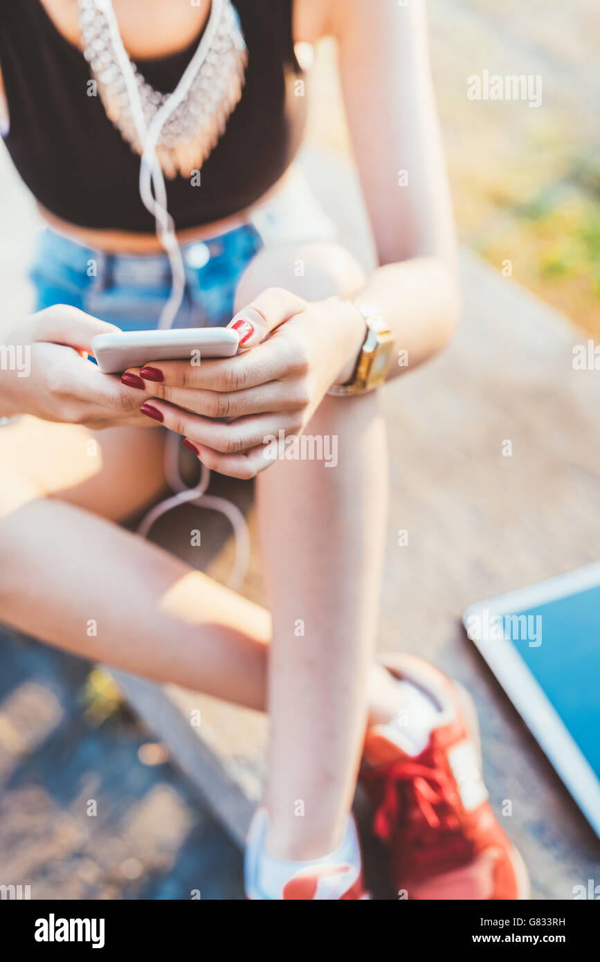 Close up on the hand of young woman tapping the screen of a smart phone - technology, internet, social network concept - Stock Image