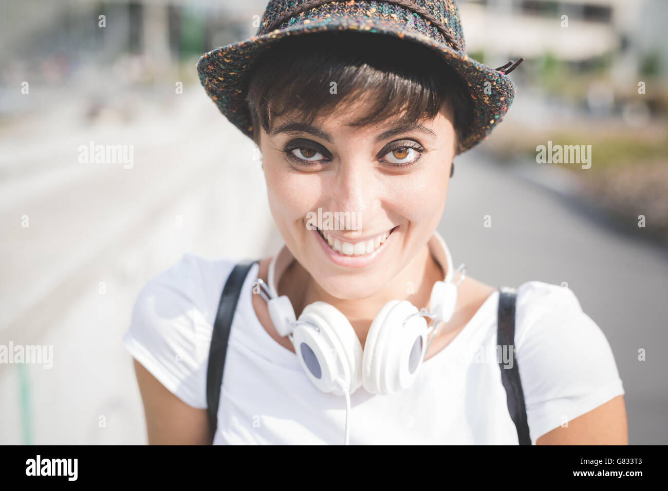 Half length of young beautiful caucasian woman wearing hat, with headphones around her neck, looking in camera smiling - Stock Image
