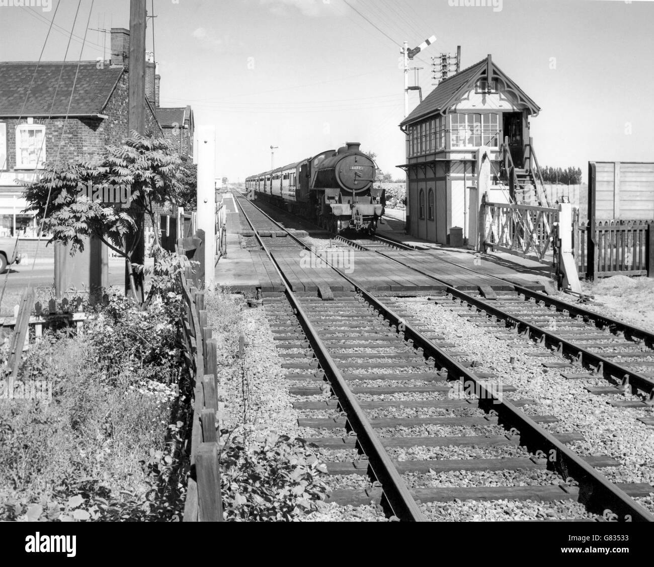 Thompson Class B1 at the head of a passenger train passes a signal box and level crossing at an unknown location - Stock Image
