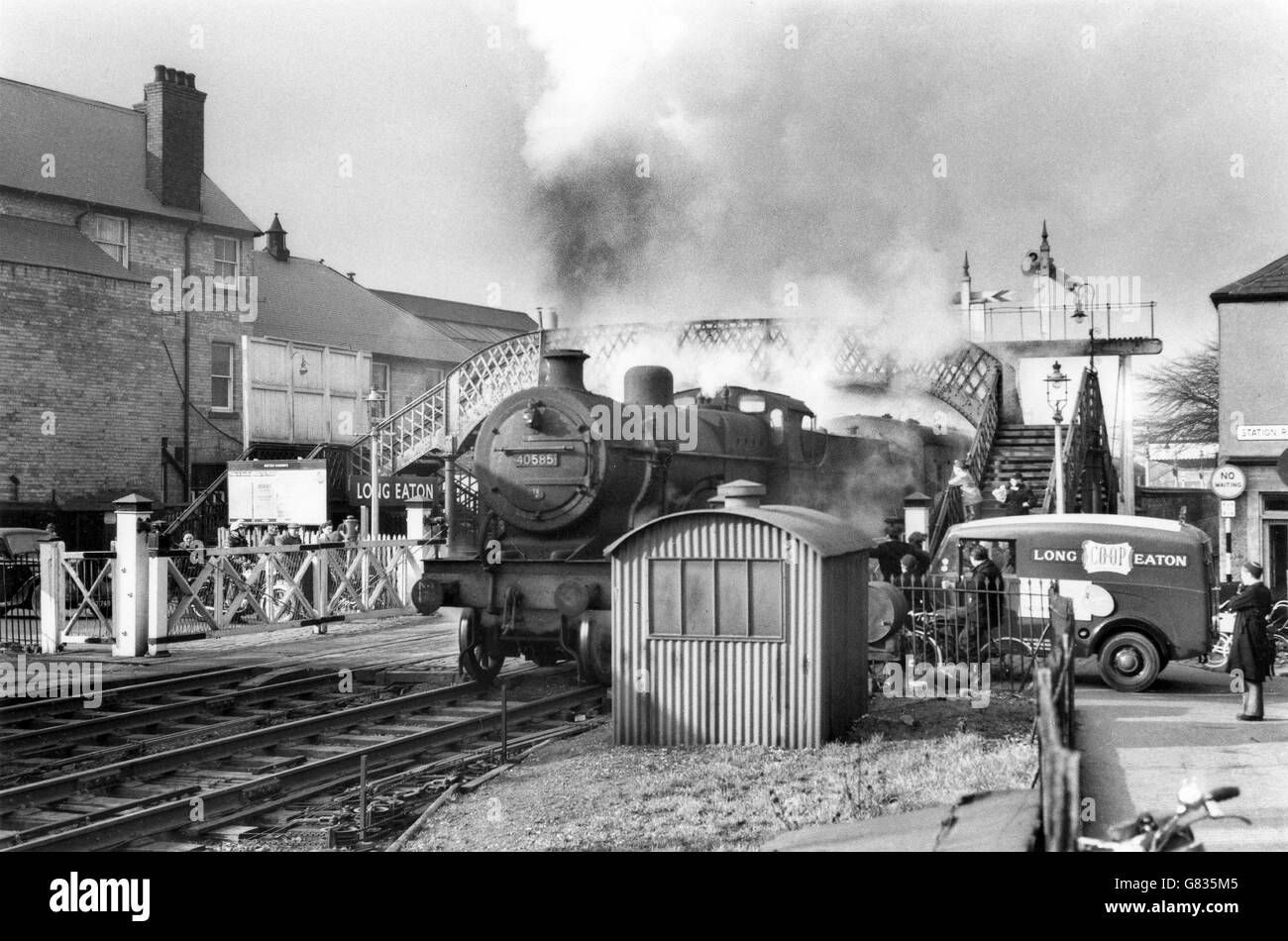 The departing train is headed by a former Midland Railway Simple 4-4-0 No. 40585  a Nottingham engine. - Stock Image