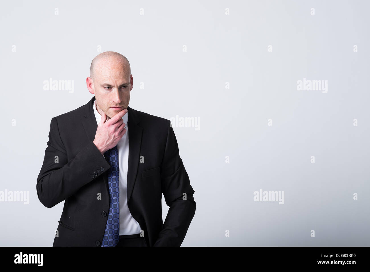 Problem solving, balding business man in a suit and tie looking thoughtful - Stock Image