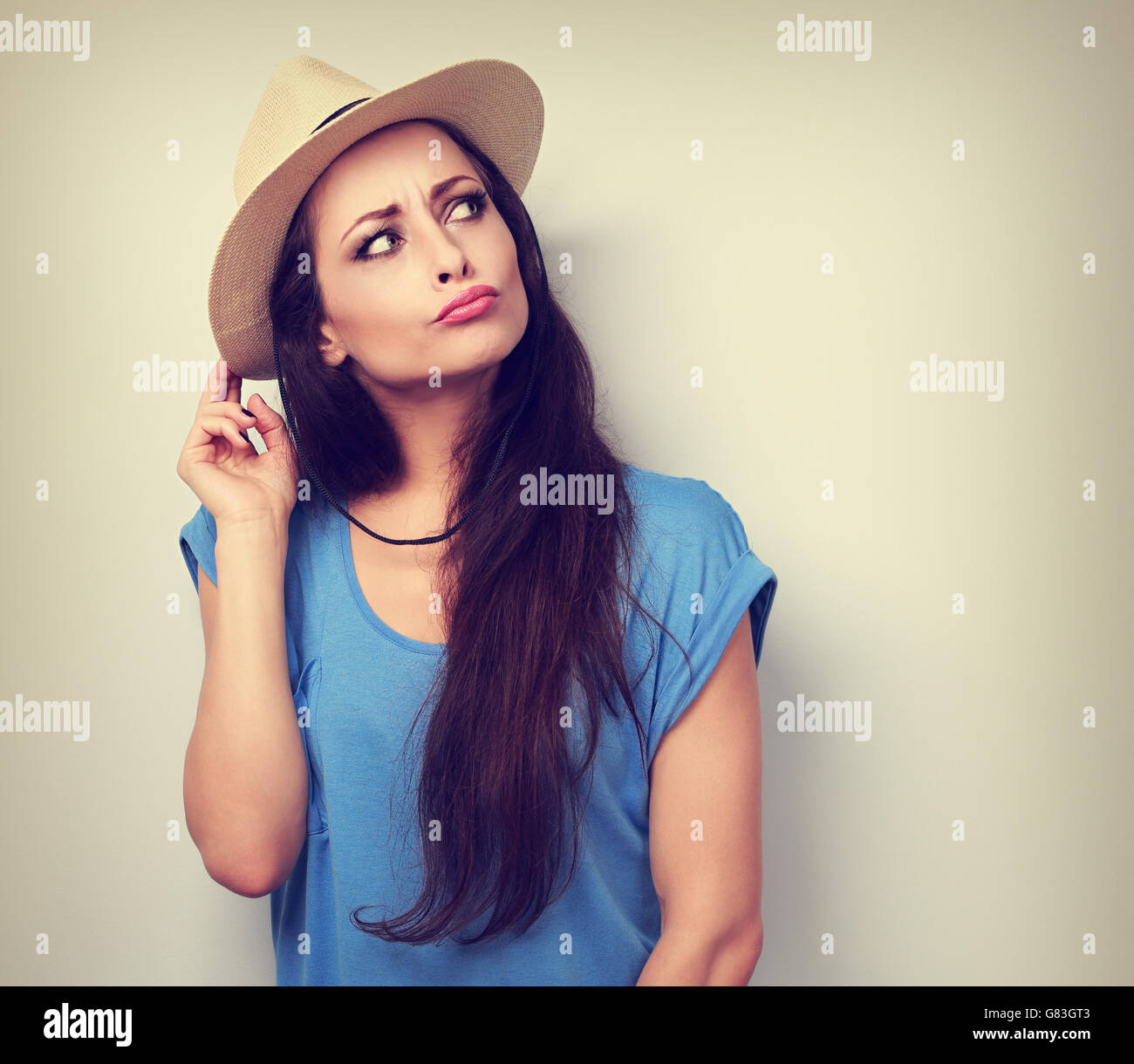 Happy humorous grimacing woman in summer hat thinking about vacation and looking. Vintage toned portrait - Stock Image