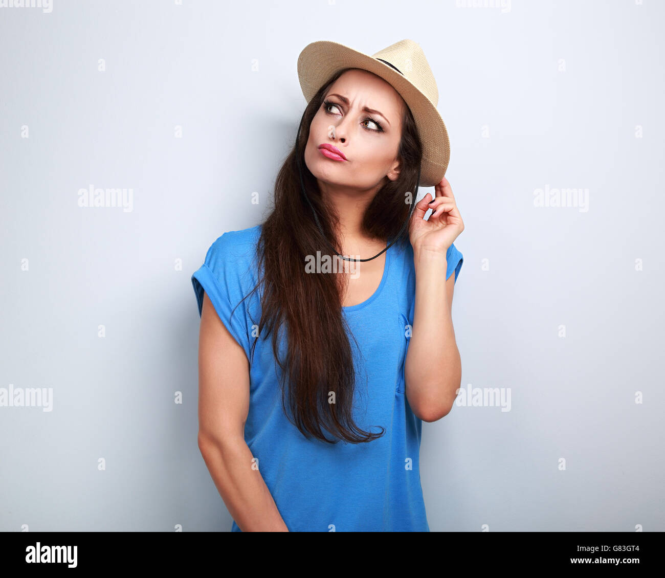Happy humorous grimacing woman in summer hat thinking about vacation and looking blue background - Stock Image