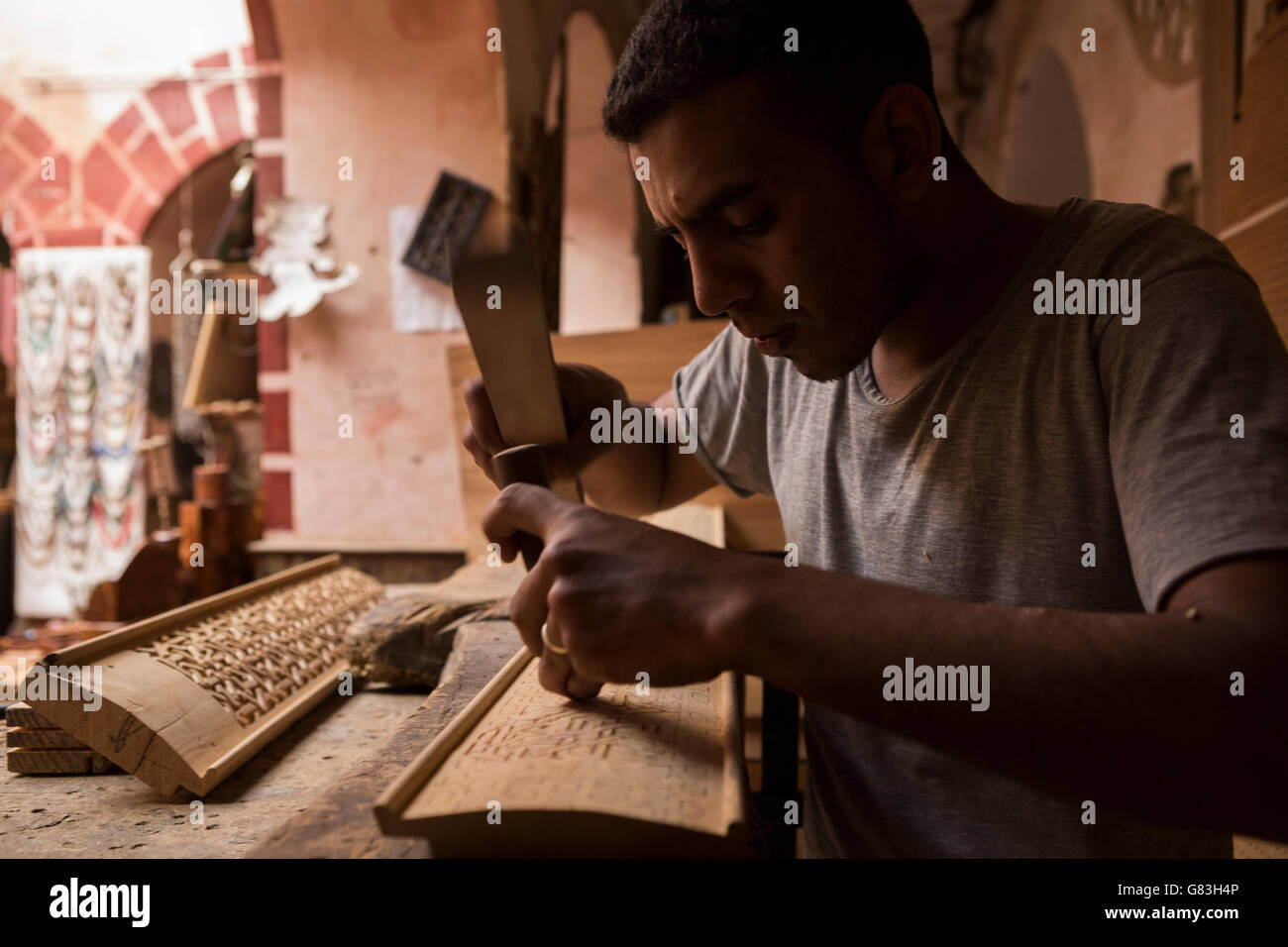 A woodworker artisan works in his workshop in the Marrakesh Medina, Morocco. Stock Photo