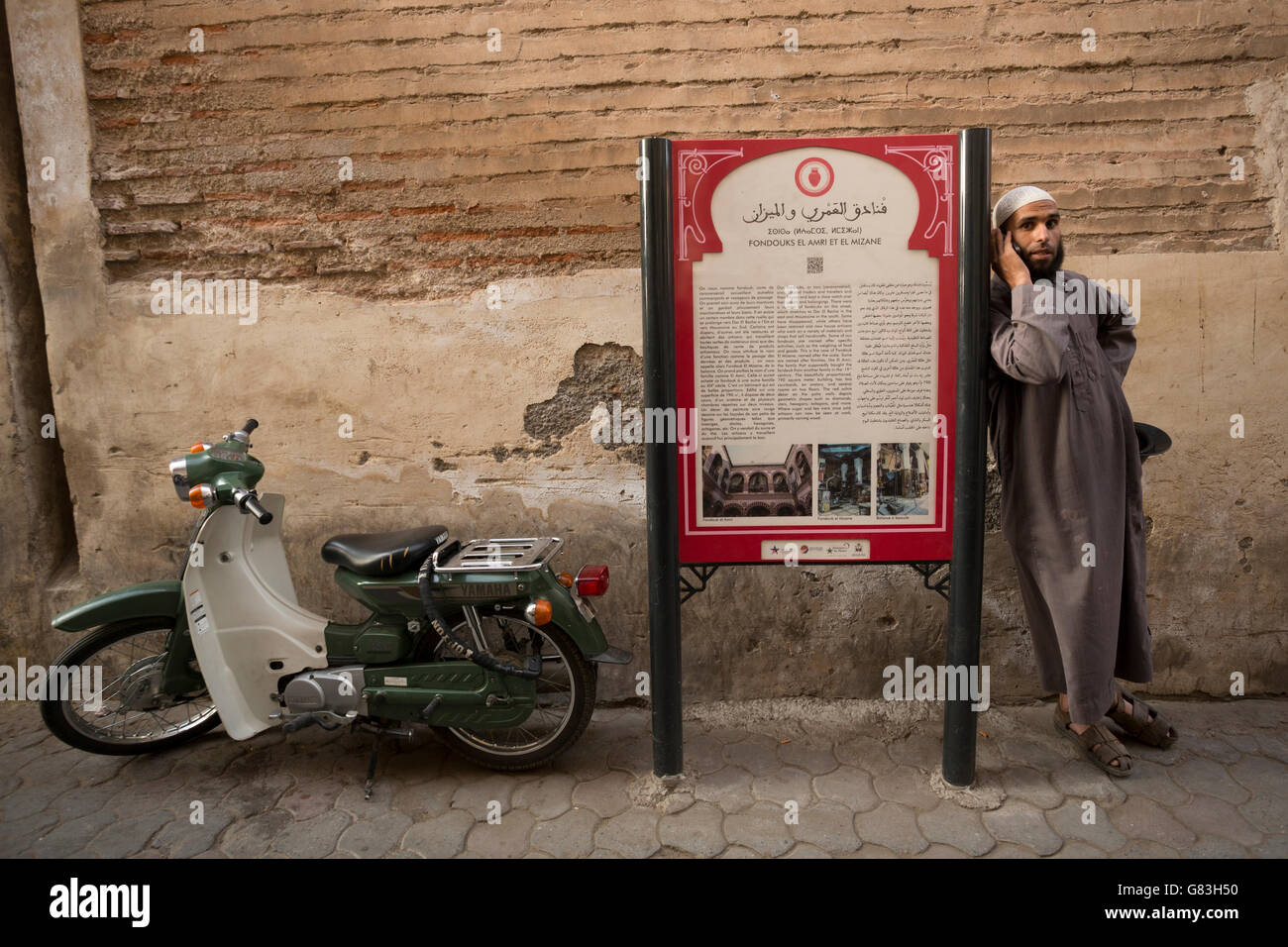 A cultural site marker stands along a narrow street in the Marrakesh Medina, Morocco. - Stock Image