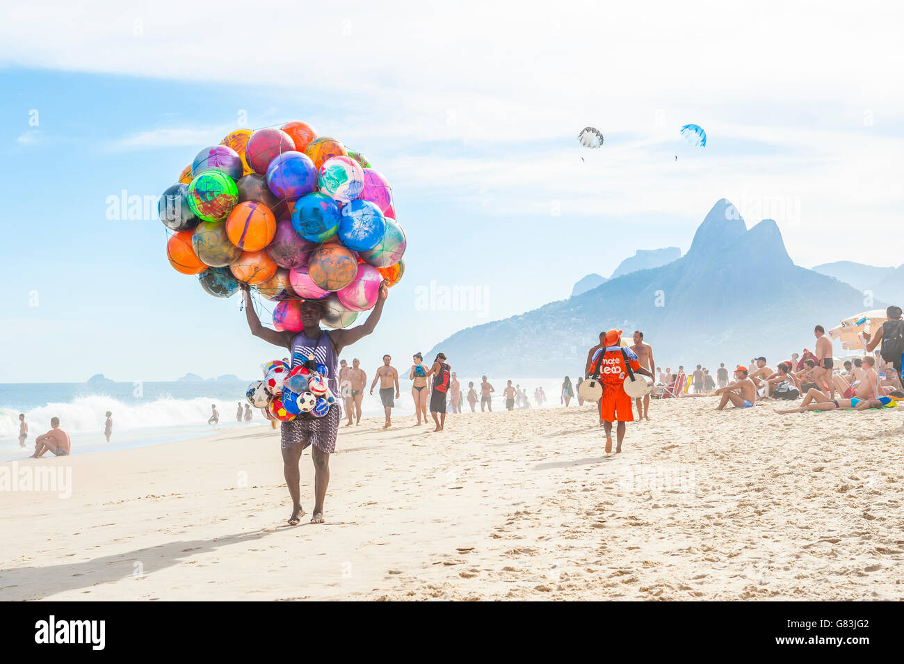 RIO DE JANEIRO - JANUARY 20, 2013: Beach vendor selling colorful beach balls carries his merchandise along Ipanema - Stock Image