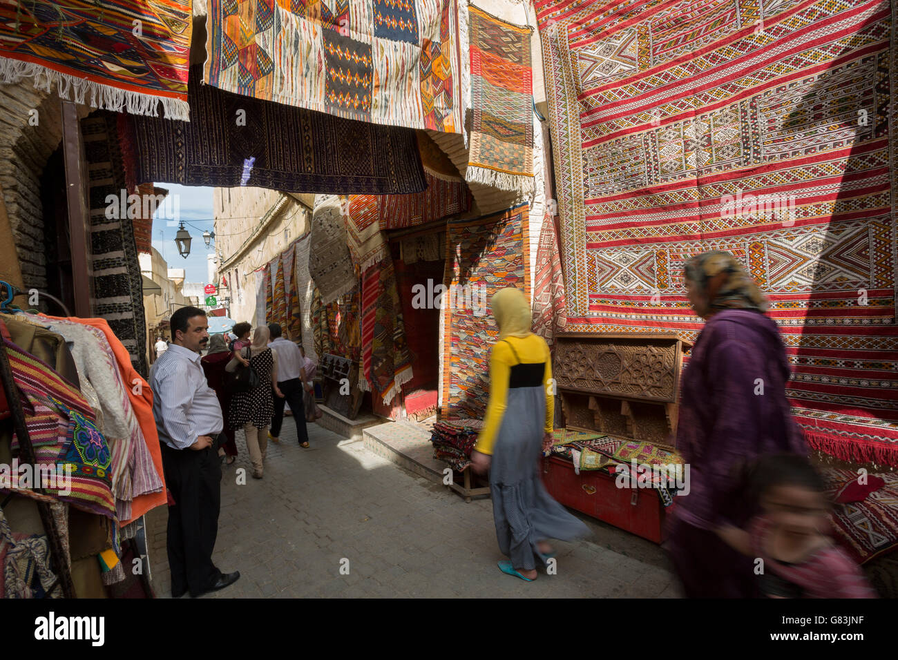 Local residents dash through the rug-lined narrow streets of the Fez Medina in Morocco. - Stock Image