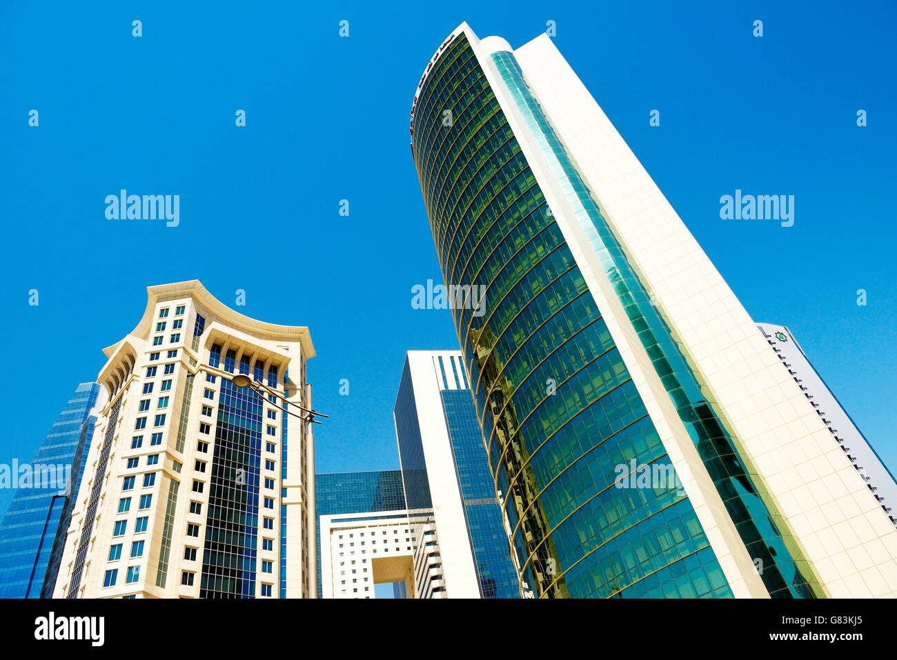 City centre West Bay area of Doha, Qatar. Majlis Al Taawon Street. Left is Burj Al Qassar Tower right is Olympic - Stock Image