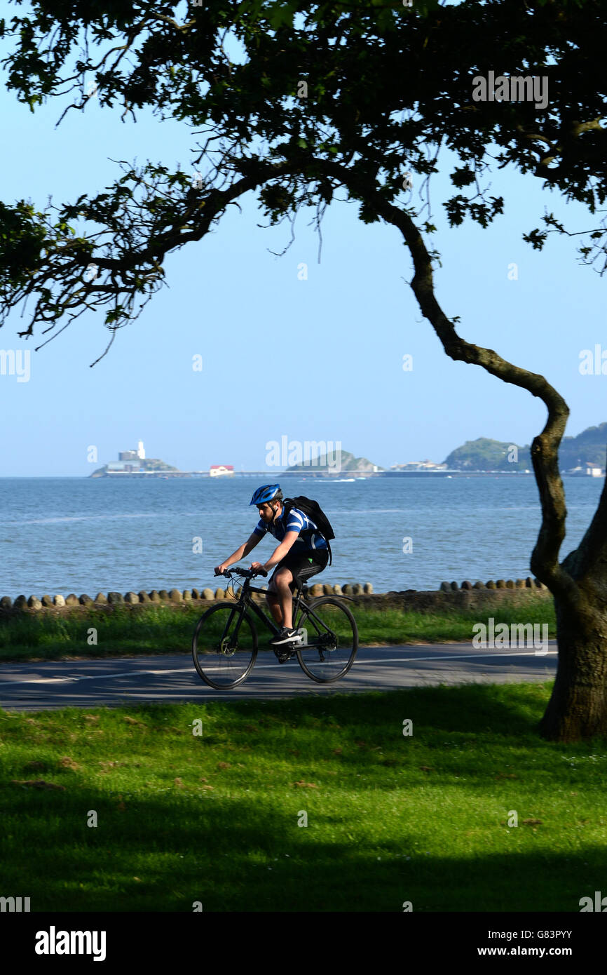 Cycling on  tree lined coast path at Mumnbles, Swansea Bay with the lighthouse lifeboat station ,pier on horizon - Stock Image