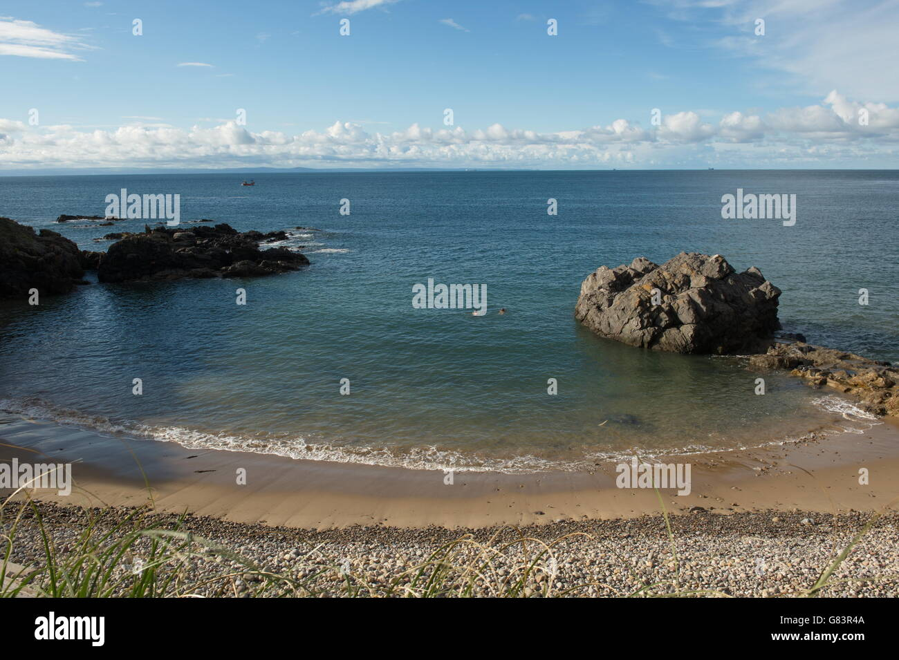 Bathers in a horse shoe shaped bay at Langland, Gower, Wales - Stock Image