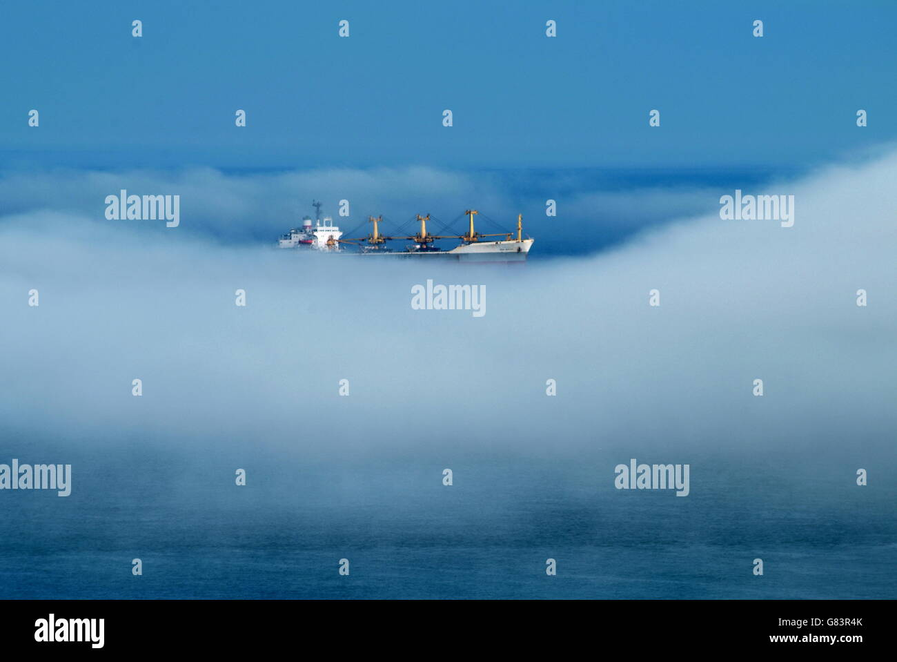 Ship in the clouds. A freighter, enveloped in fog appears to float in the sky on a sea of mist Stock Photo