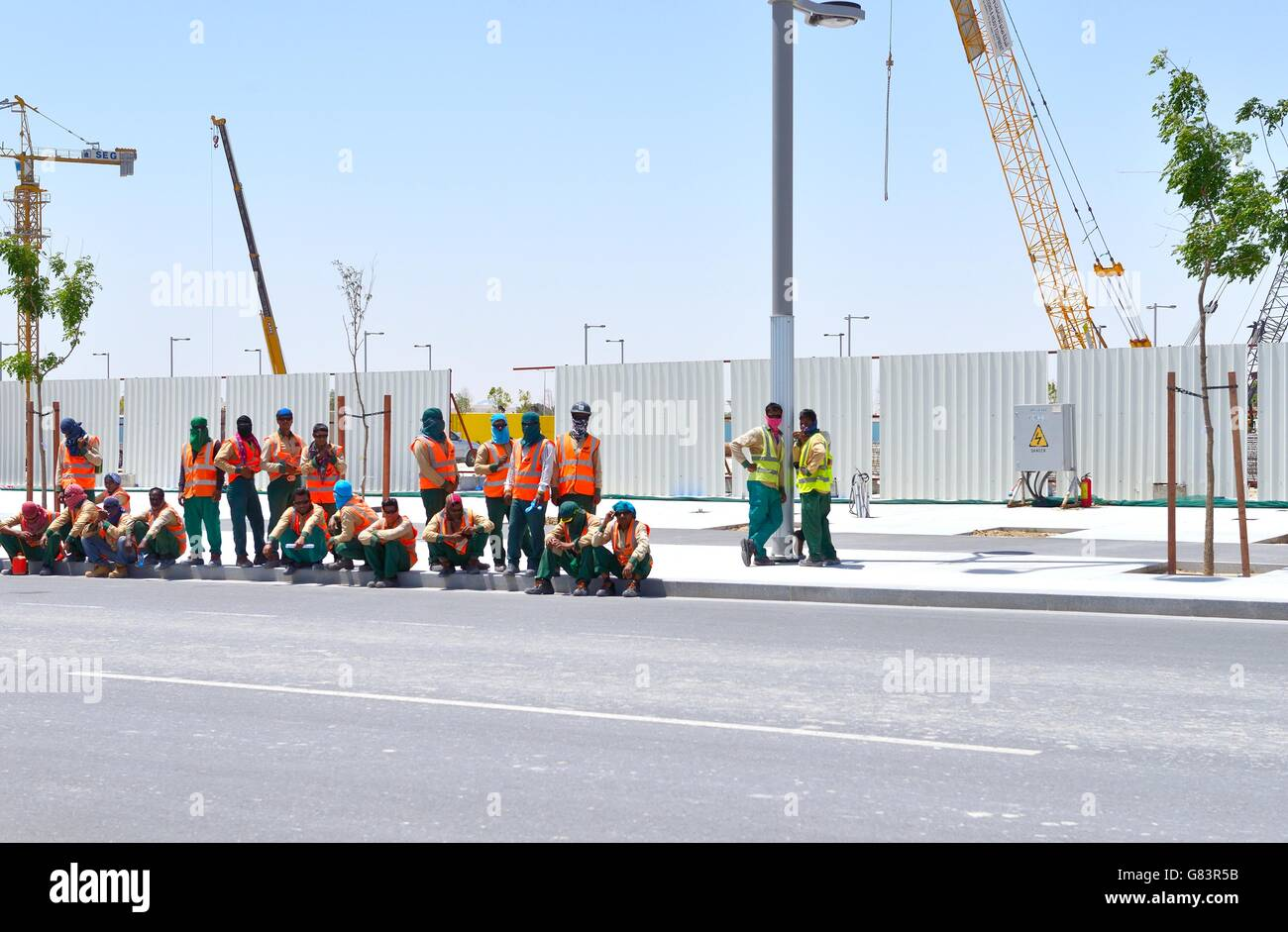 Marina District of rapidly developing new city of Lusail, Qatar. Immigrant building site construction workers wait Stock Photo