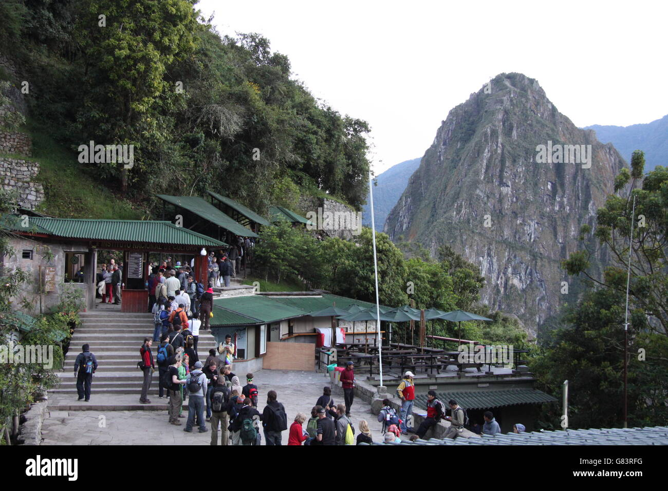 Entrance to the Machu Picchu historical site just after dawn, with people waiting to enter, with Huayna Picchu or - Stock Image