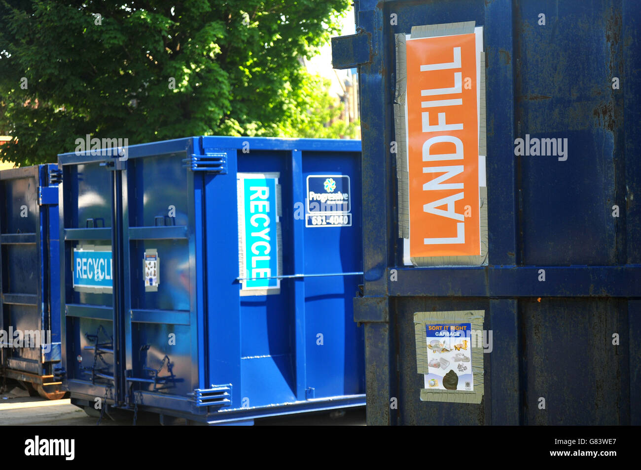 Large landfill and recycling containers placed at the side of a city festival in London Ontario. - Stock Image