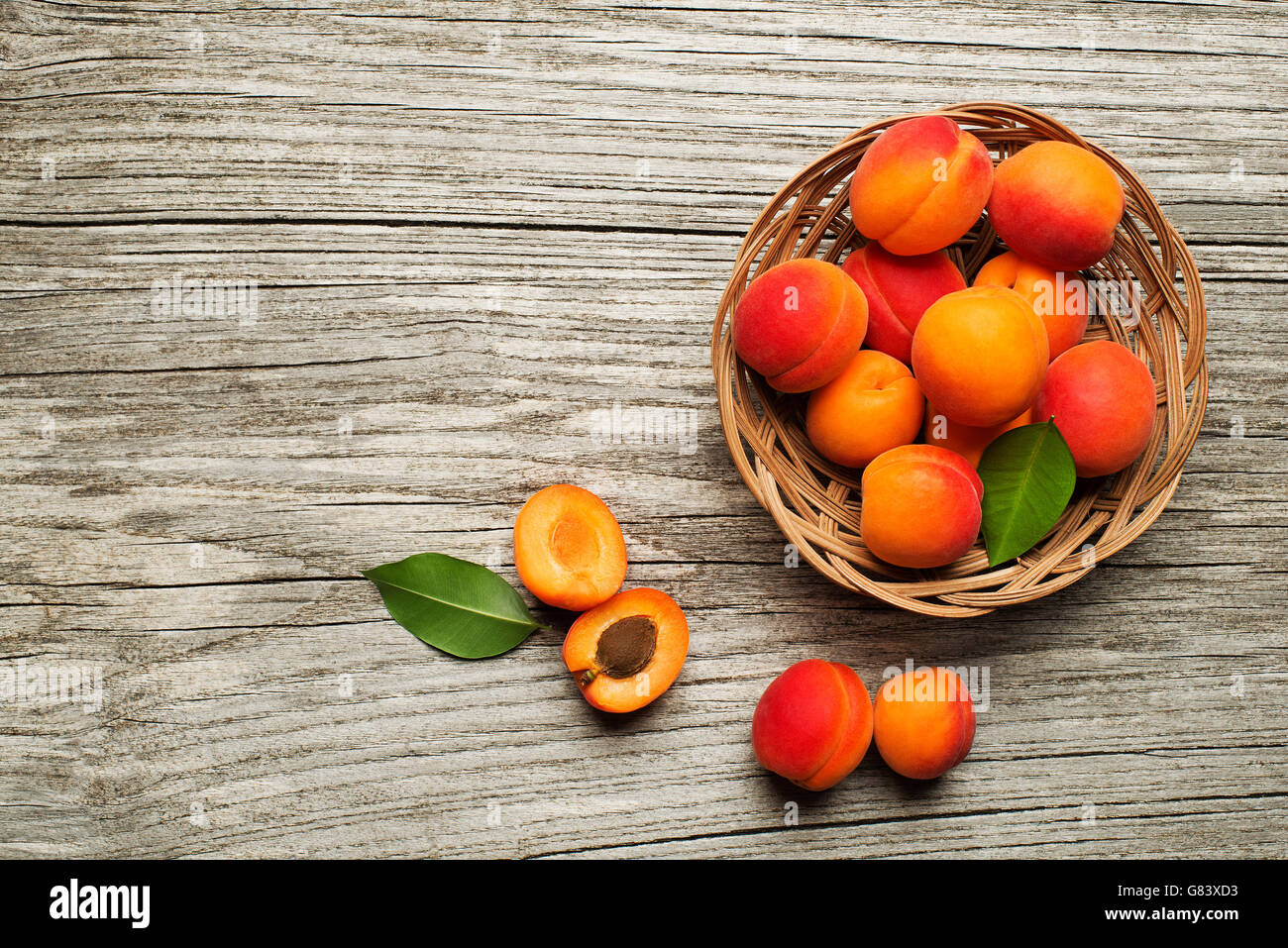 Fresh cut apricot fruits on wooden background - Stock Image