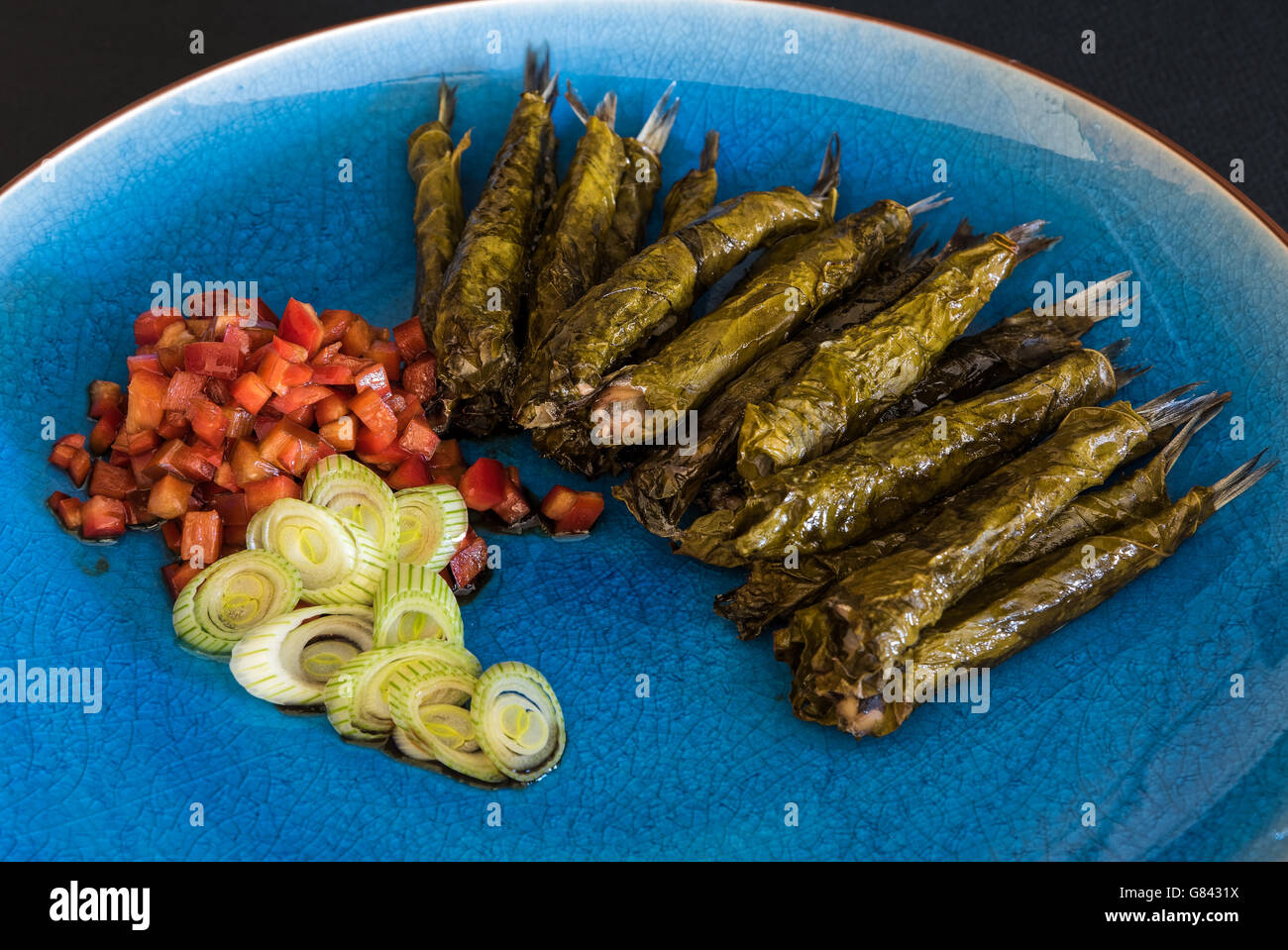 Anchovies in vine leaves, served with tomato salad and onions in blue plate - Stock Image