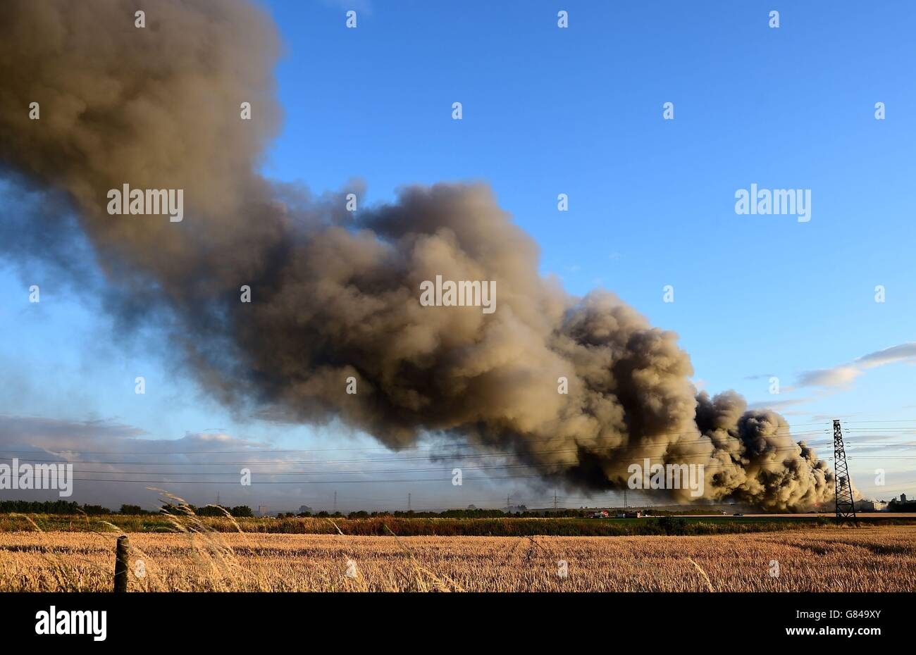 Firefighters and officers tackle a fire at a pallet yard on East Hall Lane, Rainham, Essex. Stock Photo