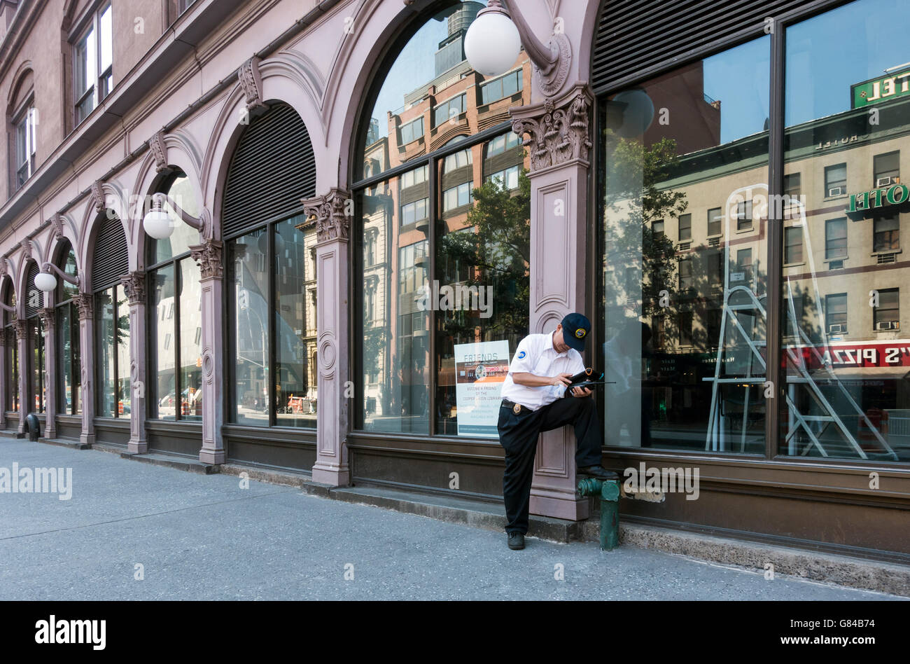 MTA bus manager checking his schedule in front of the Foundation Building near Astor Place in the East Village, - Stock Image