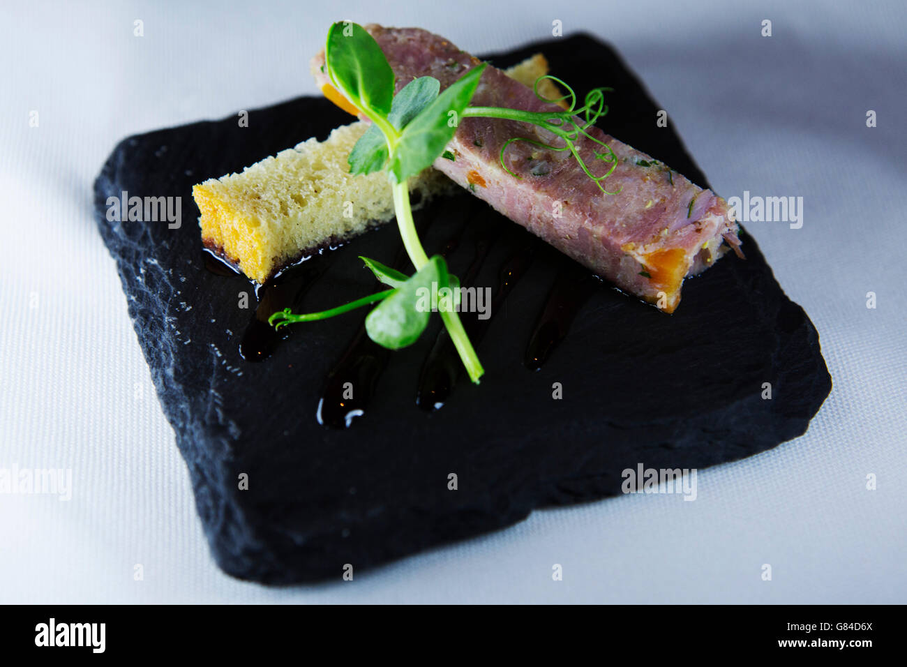 An amuse-bouche of ham hock served on slate served in Northumberland, England. - Stock Image