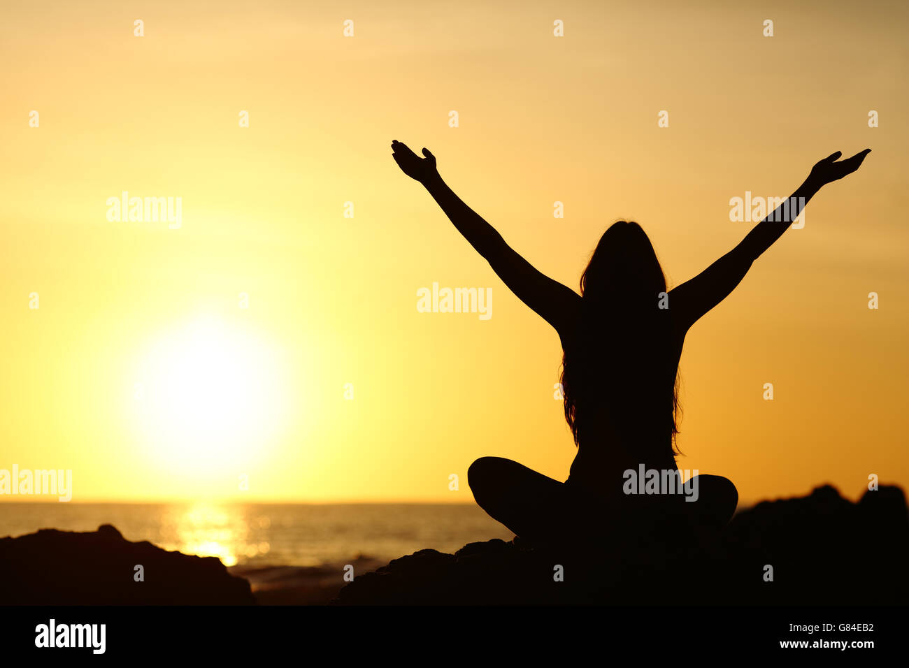 Back view portrait silhouette of a happy woman raising arms in a new day looking at warm sun at sunrise - Stock Image