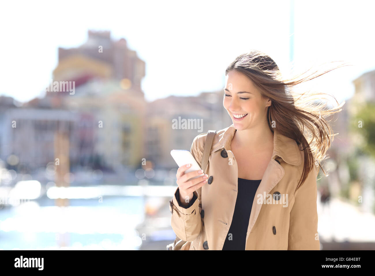 Happy beautiful woman walking and writing or reading sms messages on line on a smart phone - Stock Image