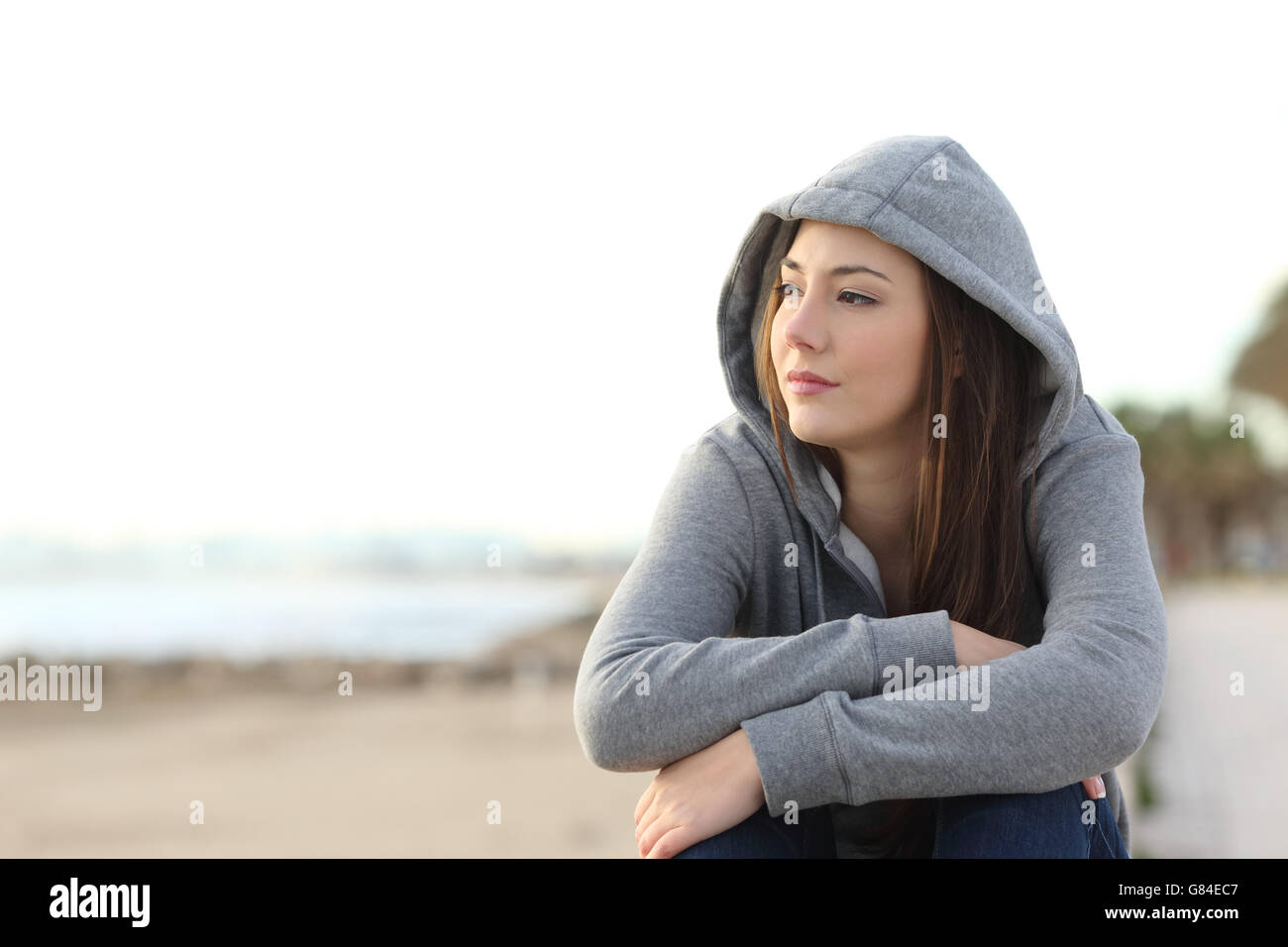 Portrait of a longing pensive teenager sitting on the beach looking away at the horizon in the morning - Stock Image