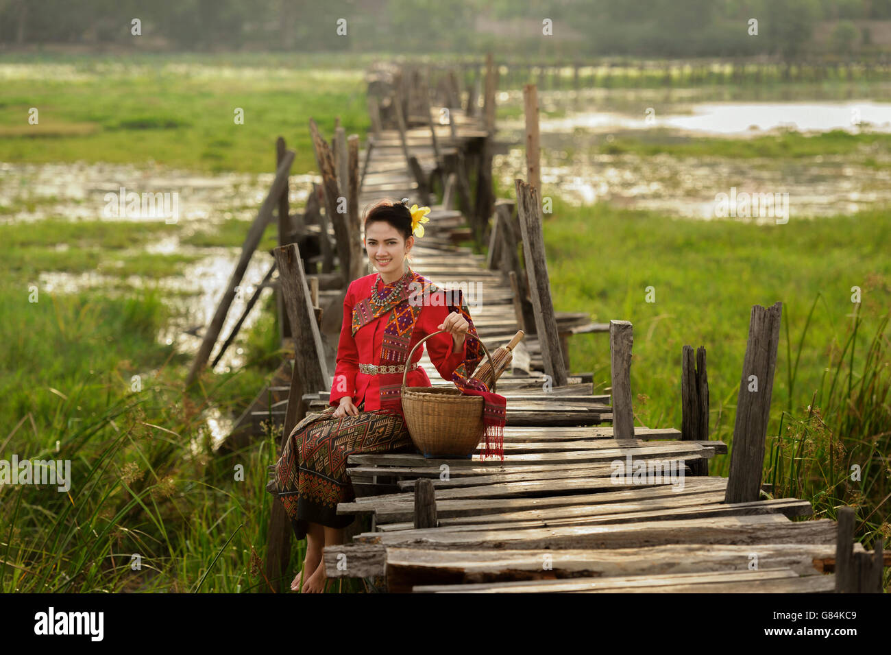 Portrait of Woman wearing traditional thai clothing sitting on bridge Stock Photo