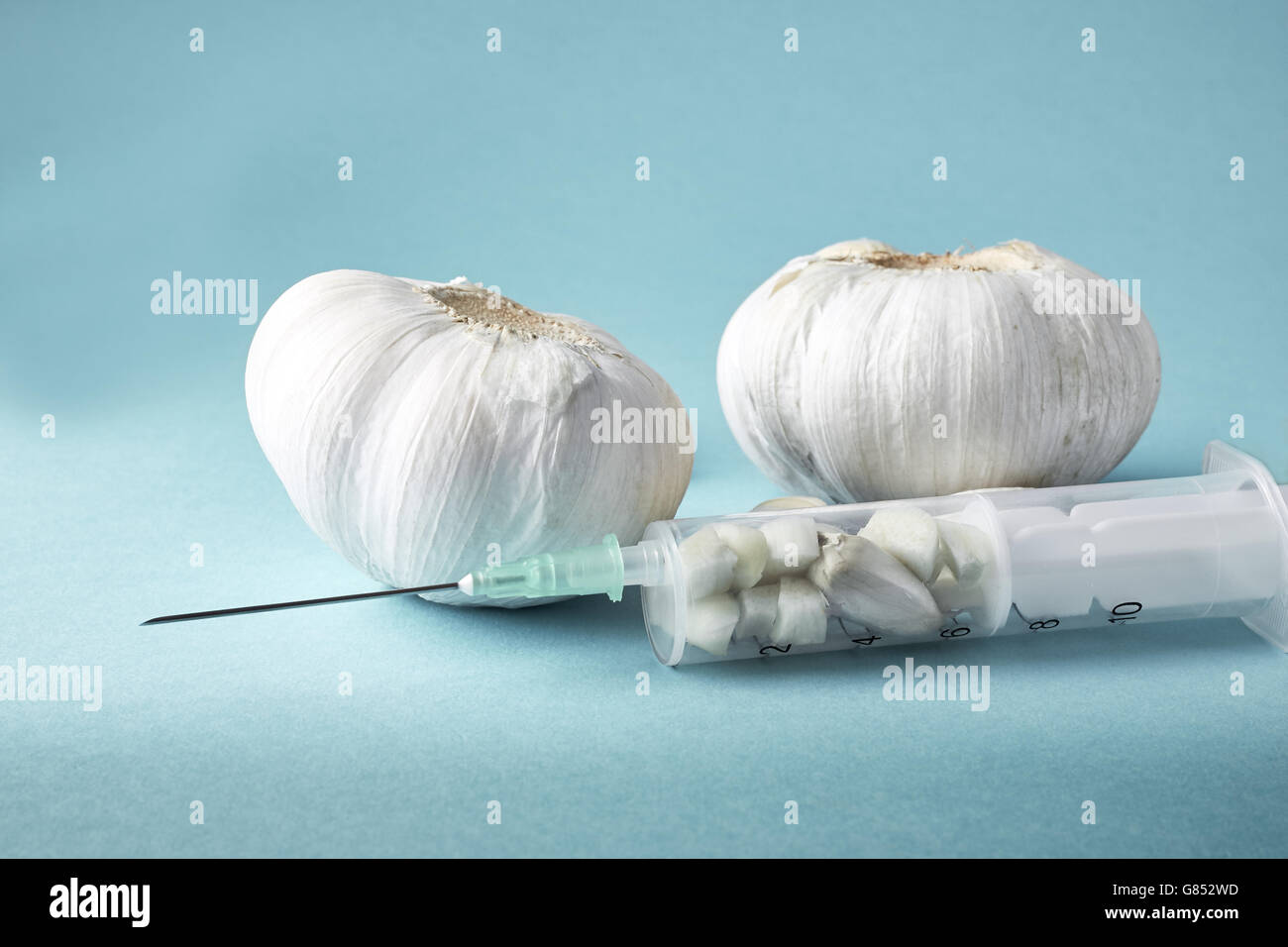 Injection with needle filled with garlic on green background. Concept image for garlic as natural antibiotic. Copy Stock Photo