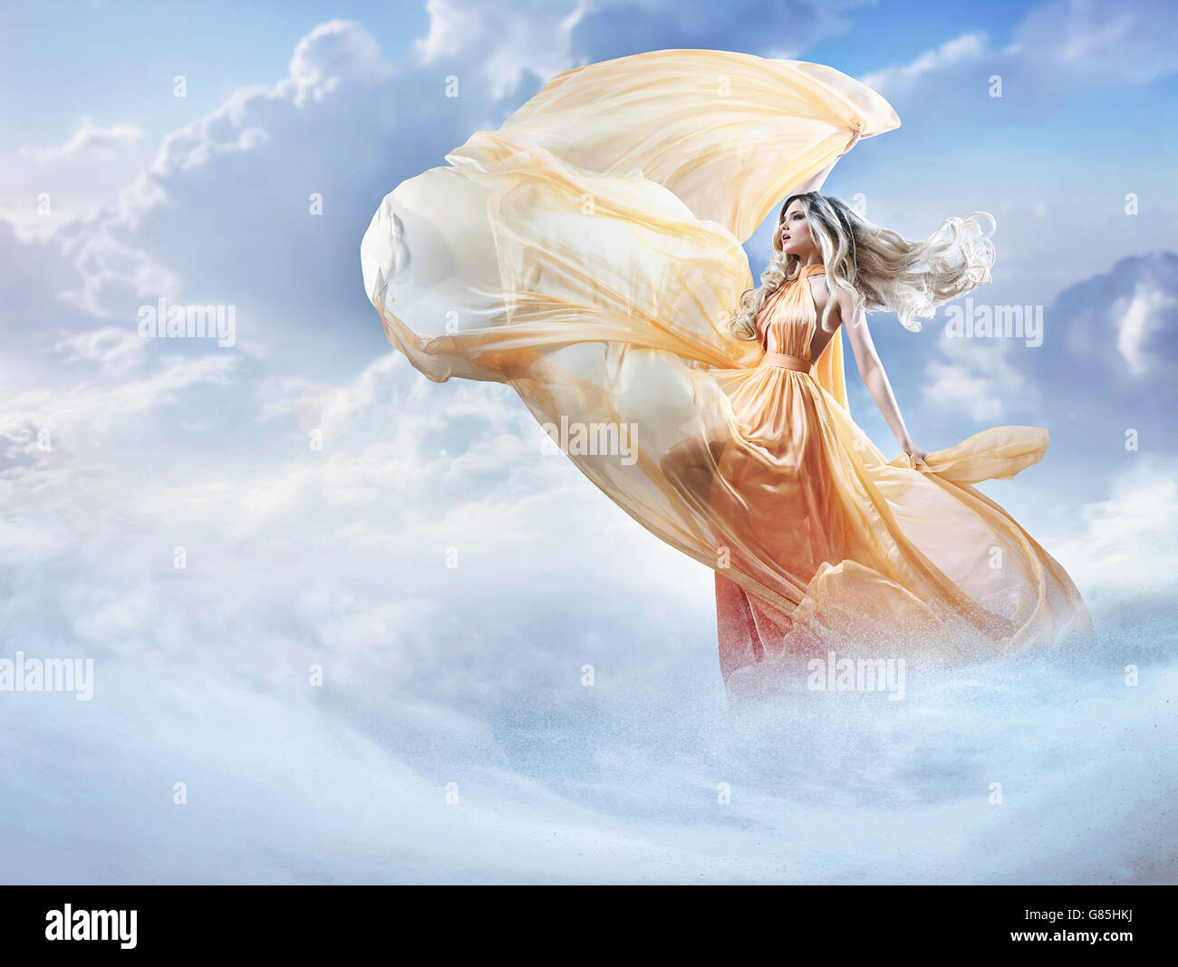 Dreamy image of a beautiful young woman in the clouds - Stock Image