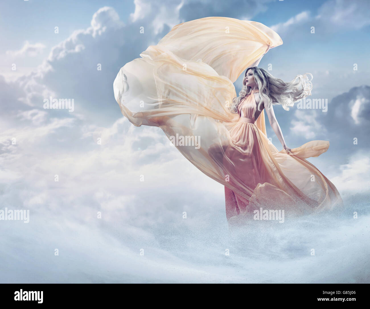 Fairy image of a beautiful young woman in the clouds - Stock Image