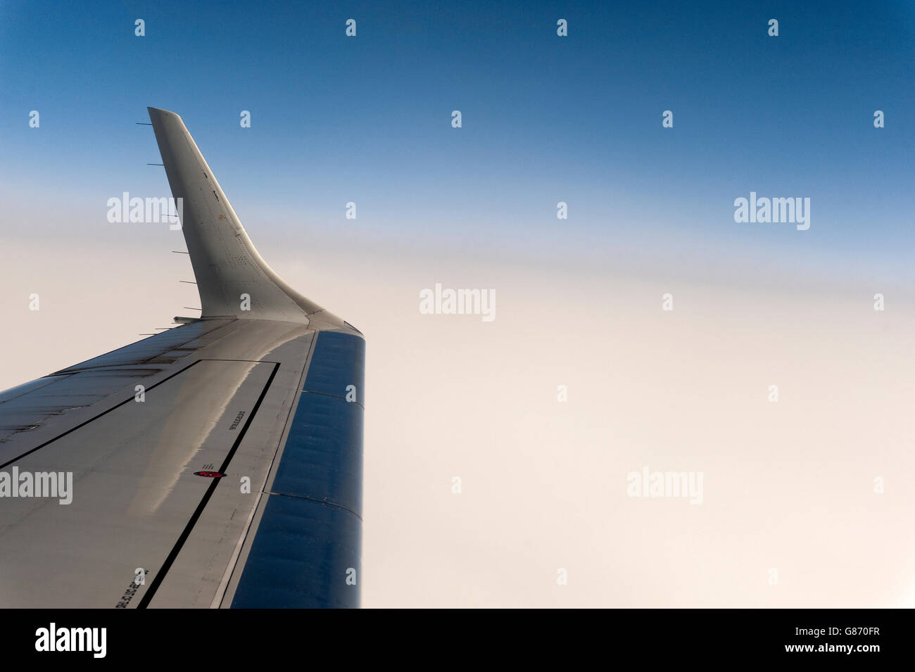 view from airplane window of wing tip and clouds - Stock Image