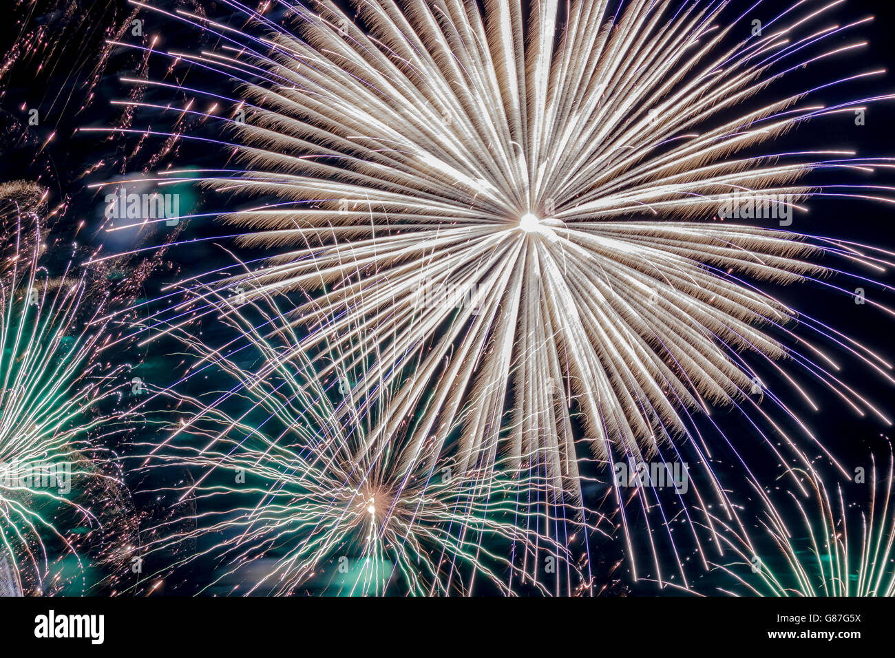 Large white burst of fireworks with blue spikes surrounded by green and aqua bursts - Stock Image