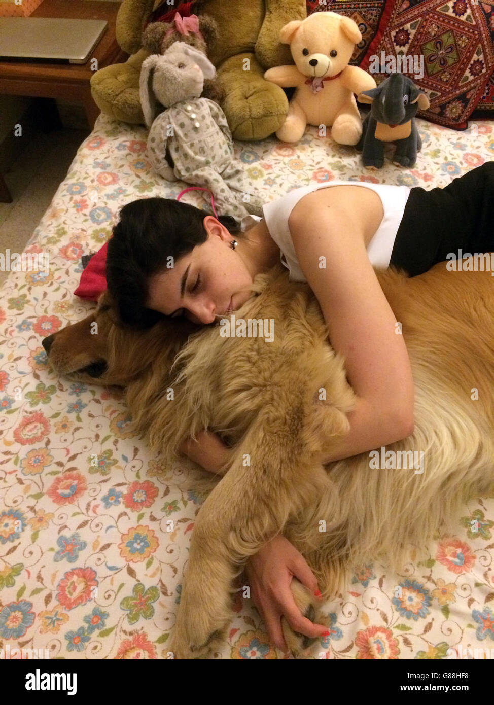 woman sleeping on bed with golden retriever dog - Stock Image