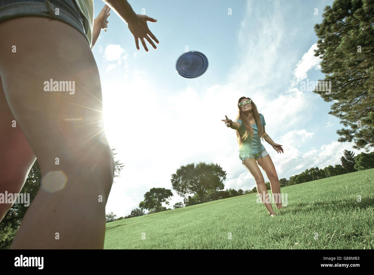 Two women playing game of Frisbee in park - Stock Image