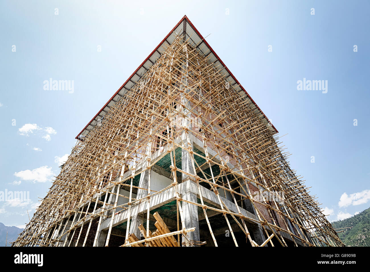 Building under construction with bamboo scaffolding. - Stock Image