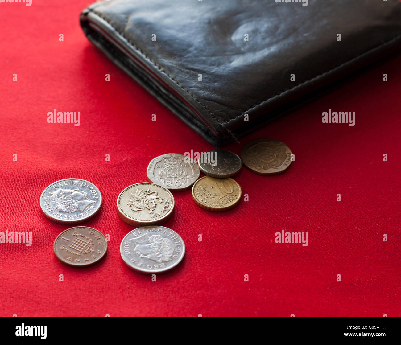 Pounds and Euro coins spilling out from leather black wallet. Red background. Stock Photo