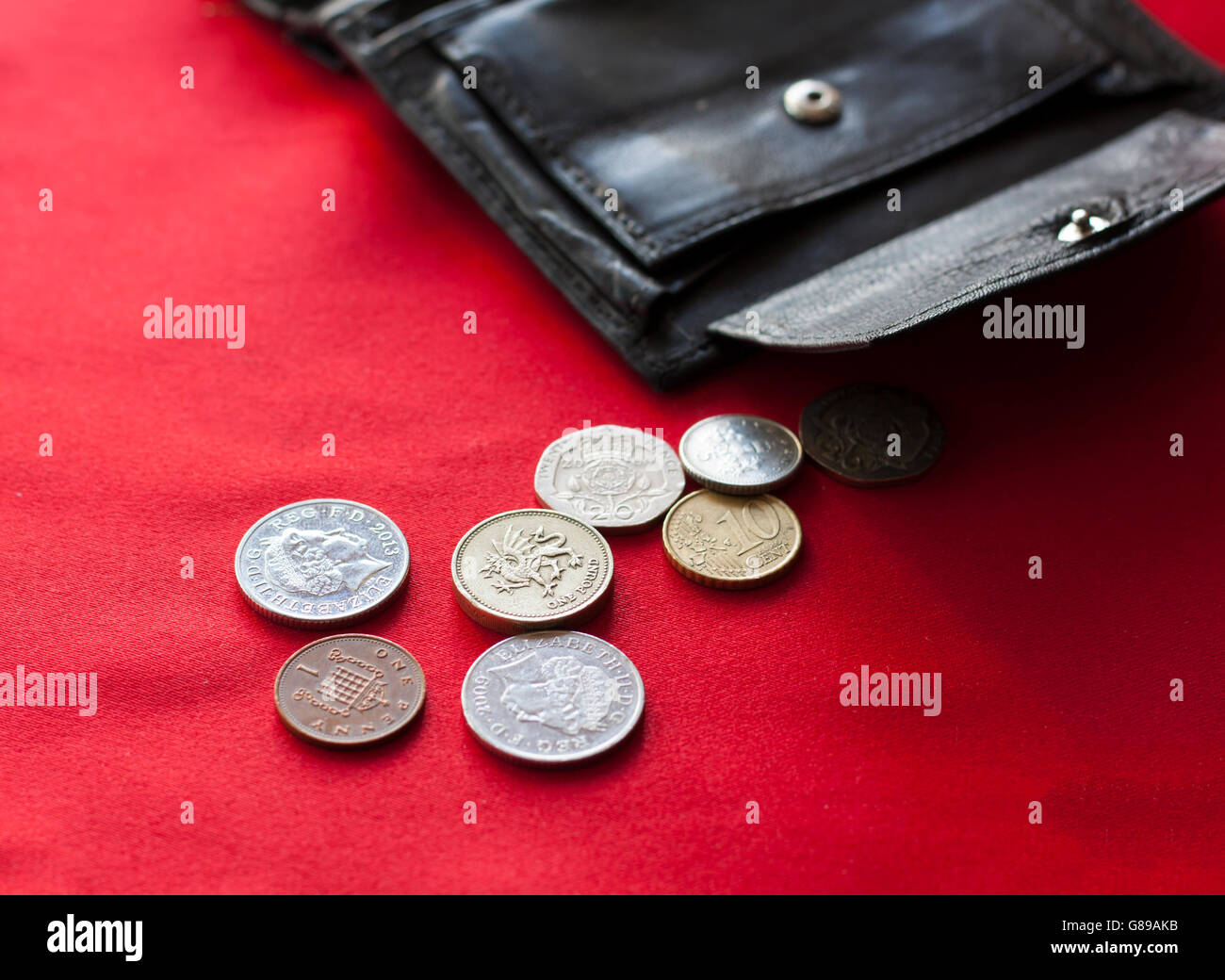 British pound and euro cent coins spilling out from open black leather wallet. Stock Photo