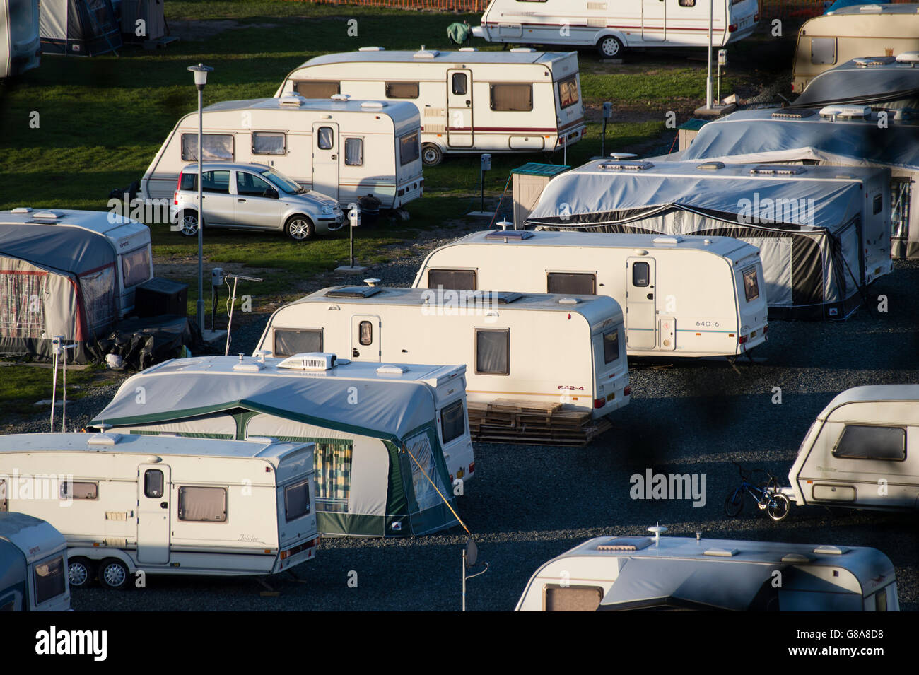 Rows of touring caravans with awnings parked up on a summer evening at the Ystwyth Caravan and Campsite, Aberystwyth - Stock Image