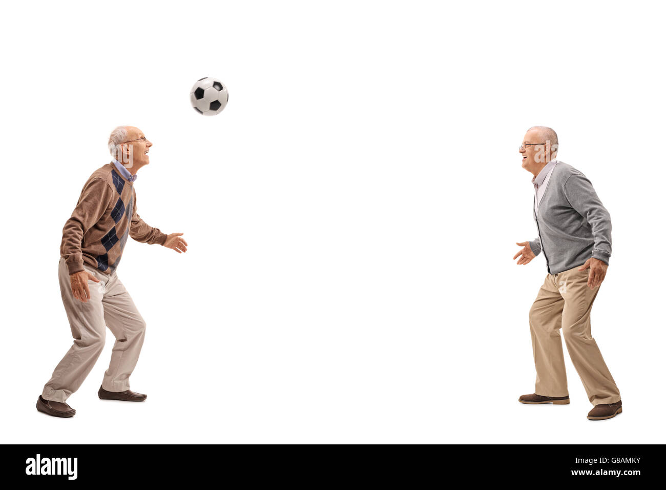 Two seniors passing a football between themselves isolated on white background - Stock Image