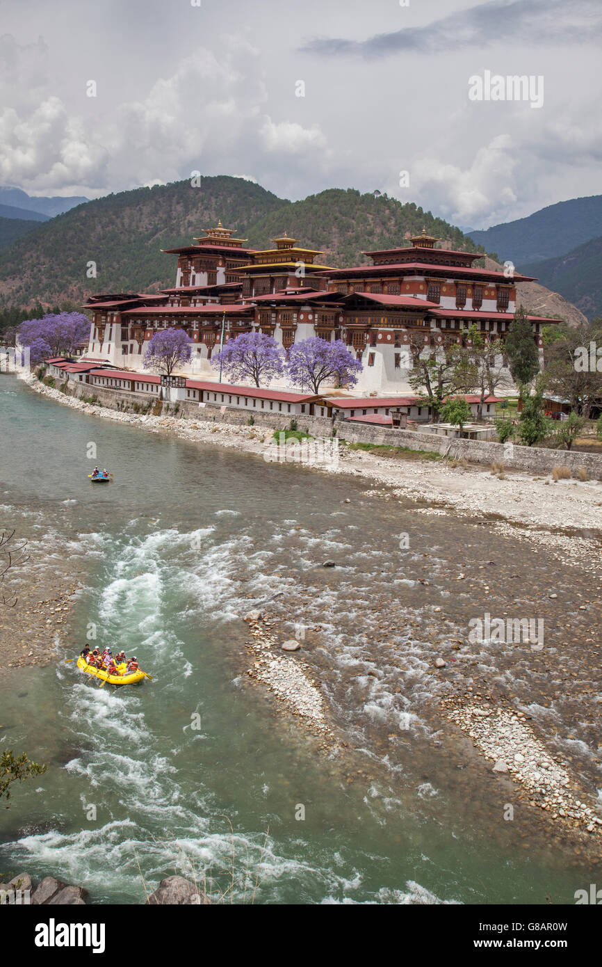 View of  the sacred Buddhist temple surrounded by colorful flowering trees and river Wangdue Thimphu Bhutan Asia - Stock Image